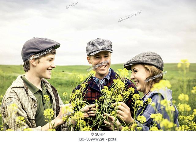 Young adults and teen boy wearing flat caps in field face to face smiling