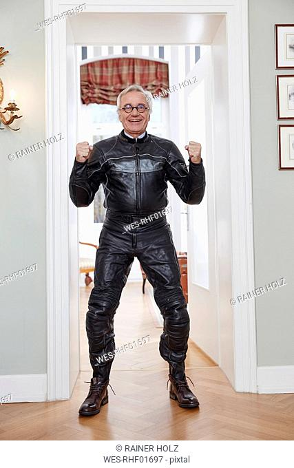 Happy senior man in motorcycle suit at home