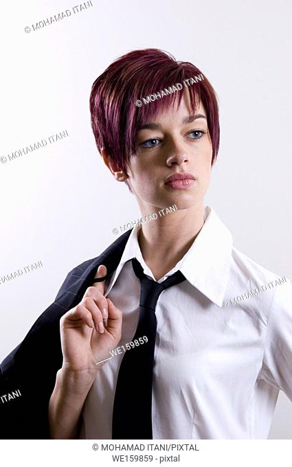 portrait of a young business woman holding her jacket behind her back