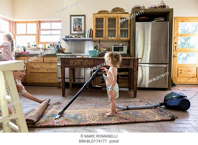 Caucasian brother and sister vacuuming rug