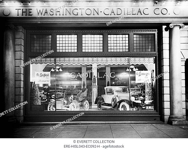 1927 Cadillac LaSalle (right) shares the showroom window with a vintage model. The Washington, D.C. dealership window compares the speed of 'Prof