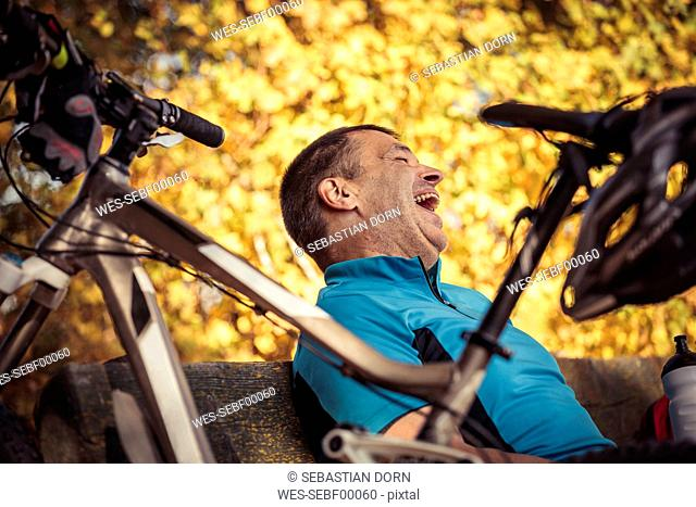 Laughing man with mountainbike having a break sitting on a bench