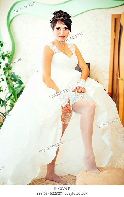 Bride putting a wedding garter on her leg
