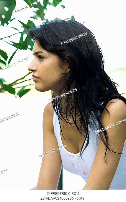 Young woman next to foliage outdoors, looking away, profile