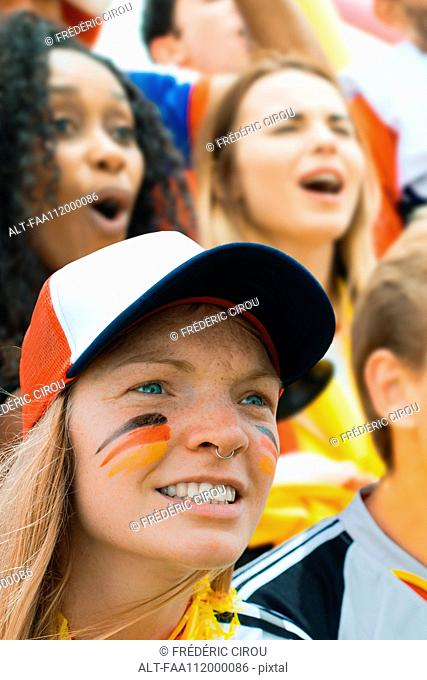 German football fan watching match with face painted in support