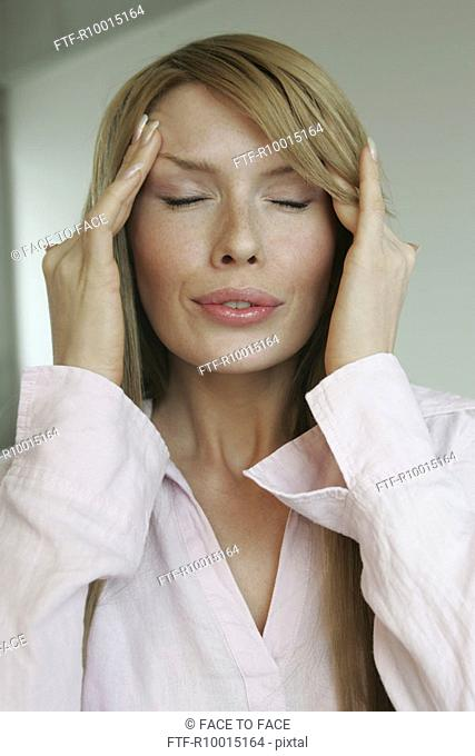 A blonde woman suffering from a severe headache