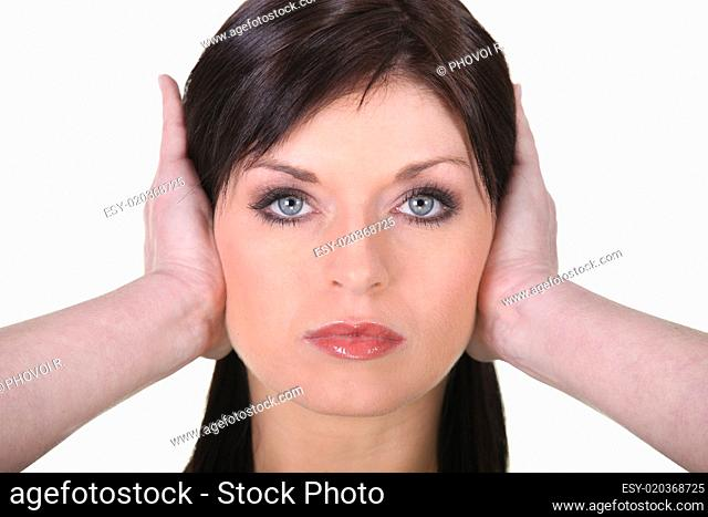 Young brown-haired woman covering her ears