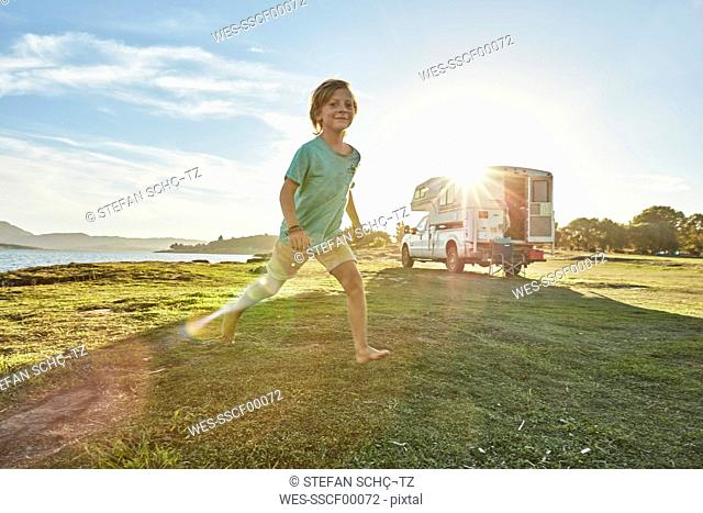 Chile, Talca, Rio Maule, boy running on meadowbeside camper at lake