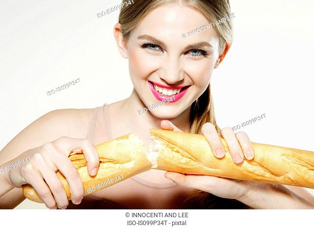Young woman breaking baguette