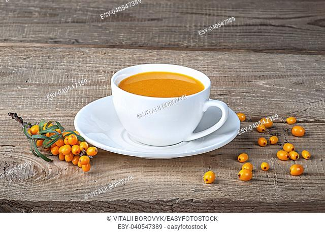 Seabuckthorn juice and berries on wooden table. Sea-buckthorn juice in a white cup on the table
