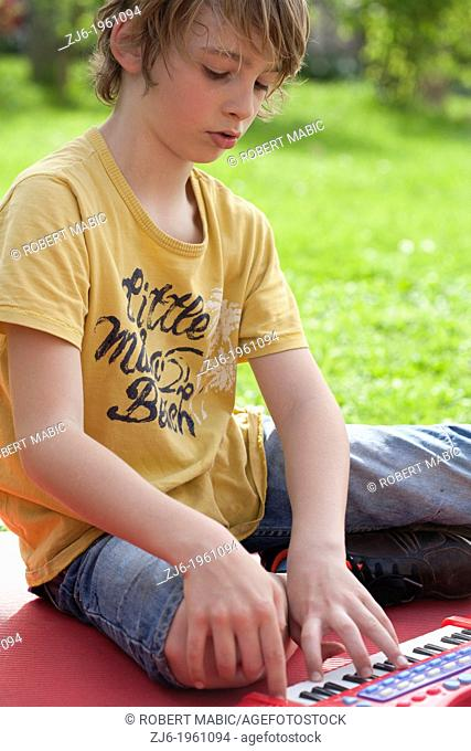 Portrait of a boy with keyboard playing outdoor in the garden