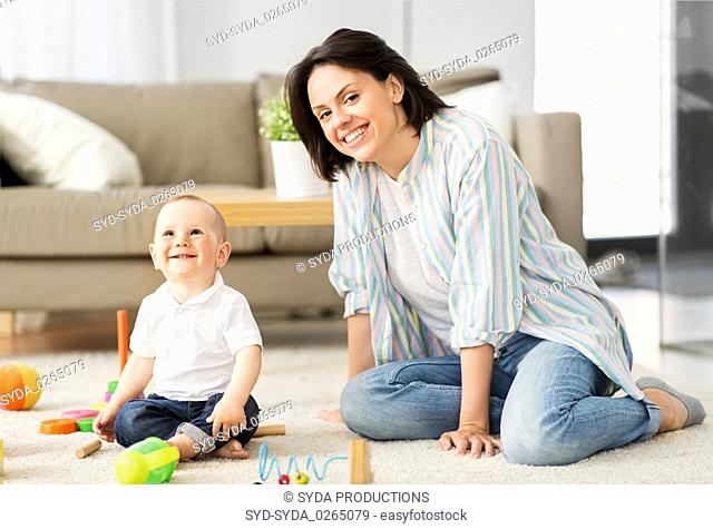 happy mother with little baby son playing at home