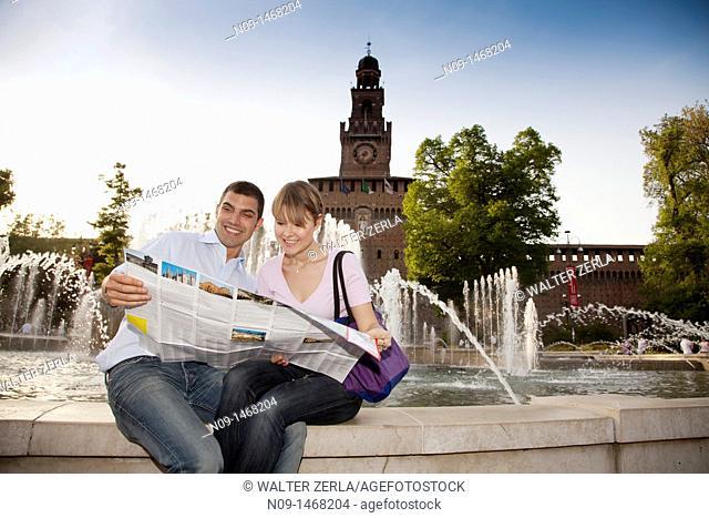 Young couple in front of the Castello Sforzesco, Milan, Italy