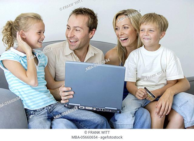 Family with 2 children is sitting with laptop and credit card on sofa