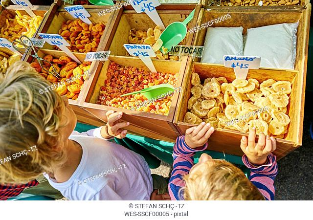 Uruguay, Montevideo, two boys standing at dreid fruit boxes on a market