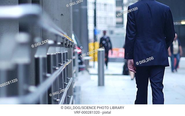 Businessman wearing a suit walking on the street with his back to the camera
