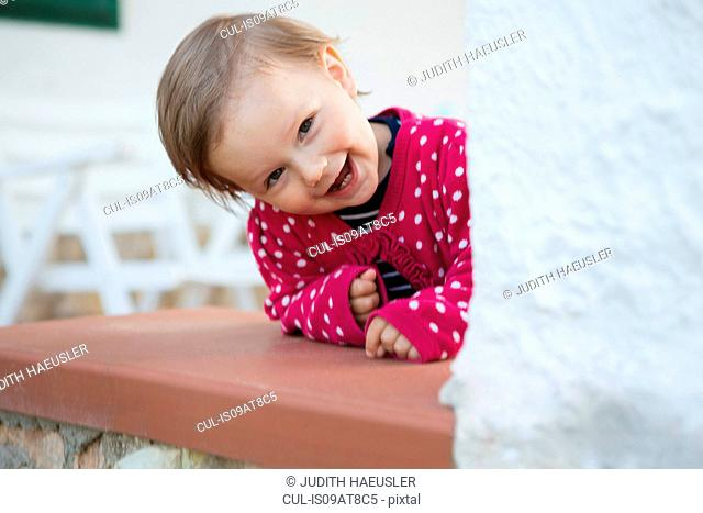 Portrait of female toddler leaning forward and peeking from table