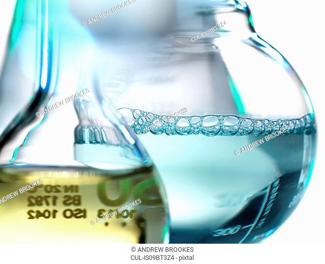 Laboratory beakers containing chemical formulas