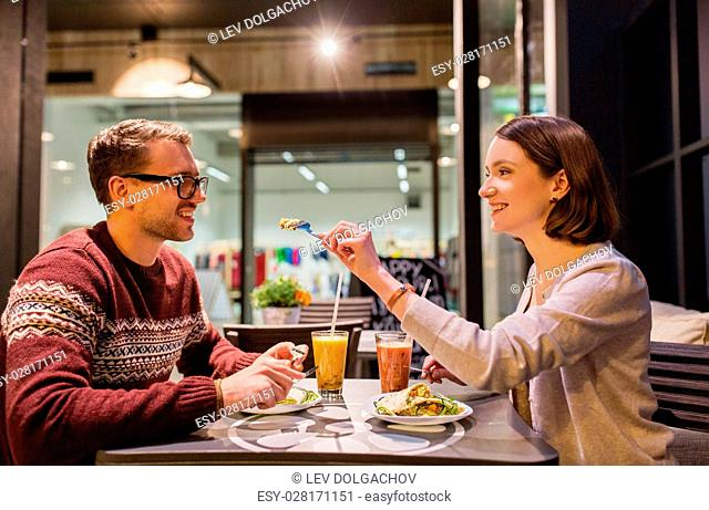 eating, vegetarian food and people concept - happy couple or friends having dinner at vegan restaurant
