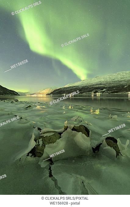 Northern Lights reflected in the cold sea frames the rocks covered with ice Manndalen Kafjord Lyngen Alps Tromsø Norway Europe
