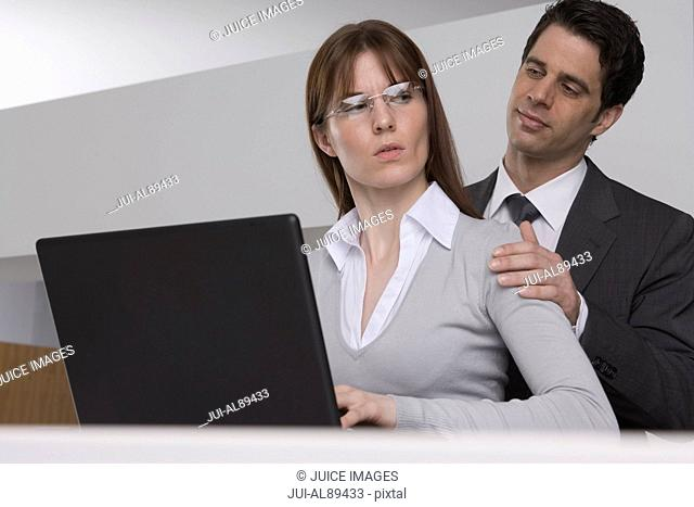 Businessman touching businesswoman's shoulder