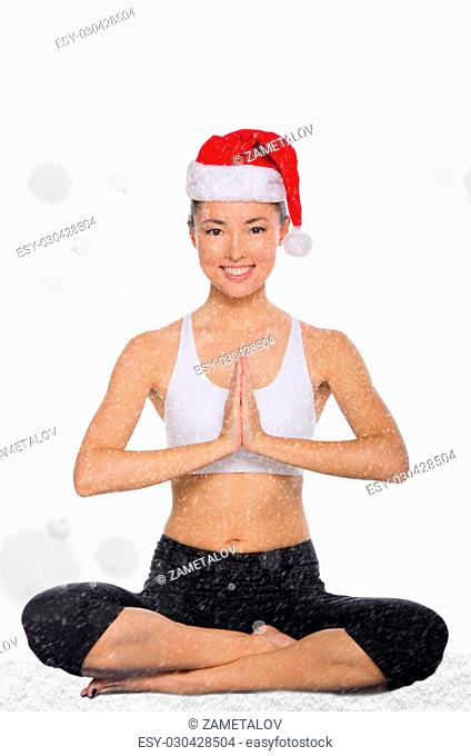 happy asian in christmas cap with snow practicing yoga isolated on white