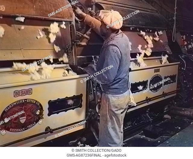 A laborer removes seeds from a cotton gin on the Hopson Plantation in Clarksdale, Mississippi, November, 1939. Note: Image has been digitally colorized using a...