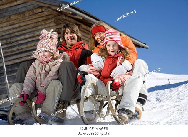 Family riding on sleds, Luesener Alm, Dolomite Alps, South Tyrol, Italy