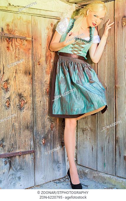 Elegantes blondes Model im Dirndl lehnt an einer alten Holztreppe.Elegant blond model in Dirndl leans at an old wooden stairs