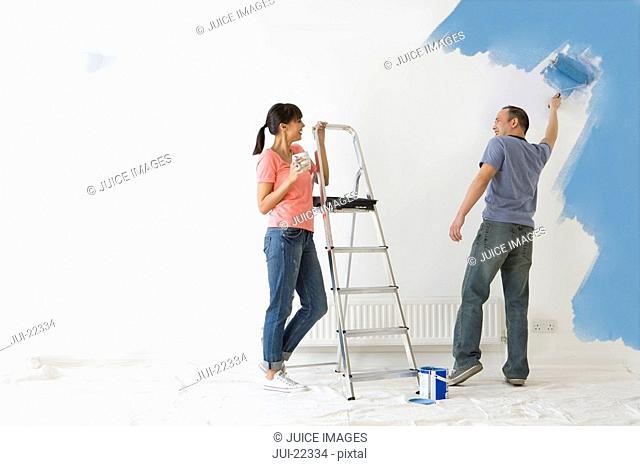 Woman leaning on ladder and watching man paint wall with paint roller