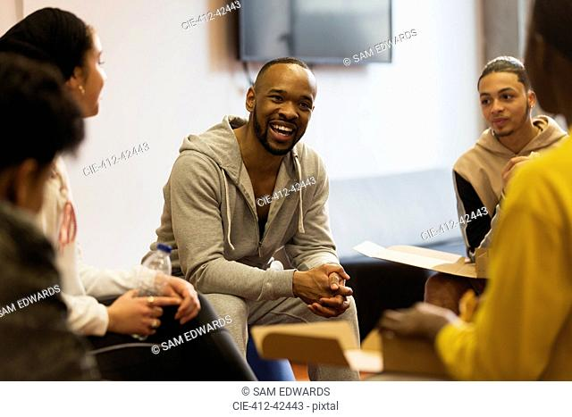 Smiling male mentor talking to teenagers in youth organization