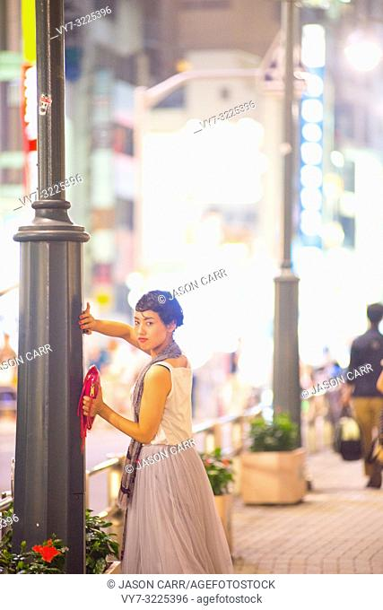 Asian female model poses for pictures in the cityscape