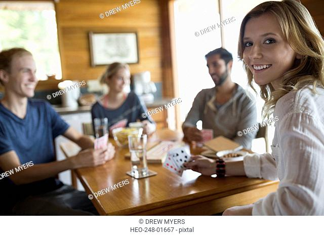 Portrait smiling young woman playing cards with friends