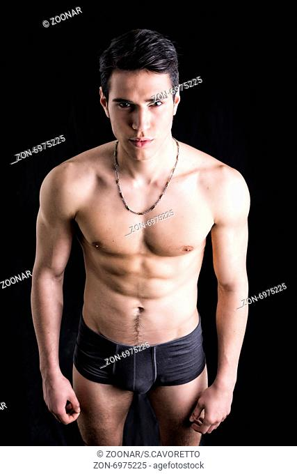 Handsome, fit young man wearing only underwear standing on black background, looking at camera