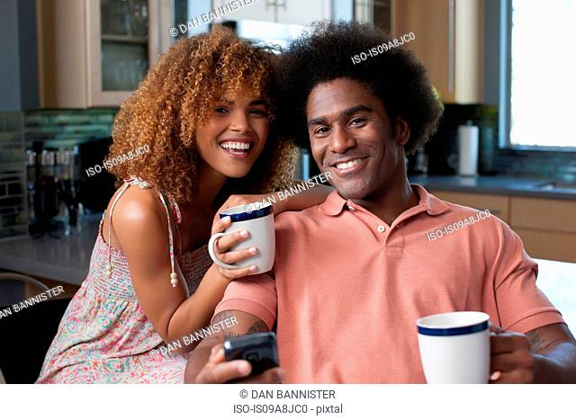 Mid adult woman and mature man holding coffee mugs, portrait