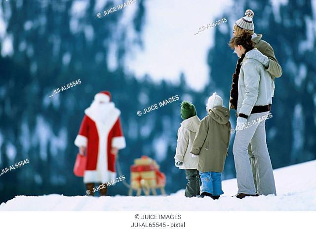 Family watching Santa Claus arrive, outdoors