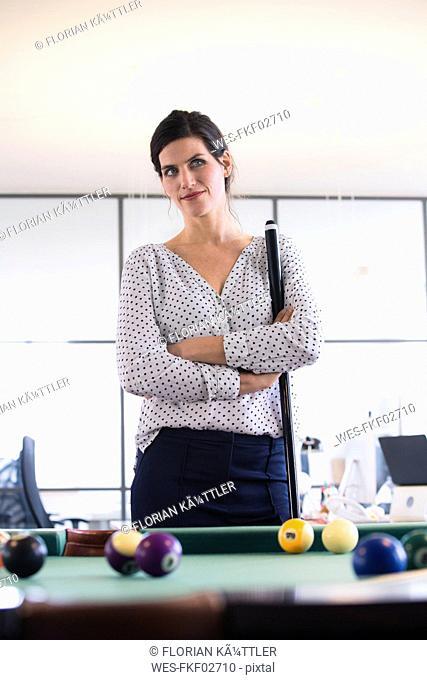Businesswoman standing at pool table, playing billard, thinking