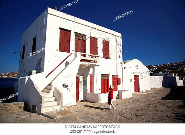 Tourist woman in front of the old Cyclades house used as Folk Museum in the town center, Mykonos, Cyclades Islands, Greek Islands, Greece, Europe