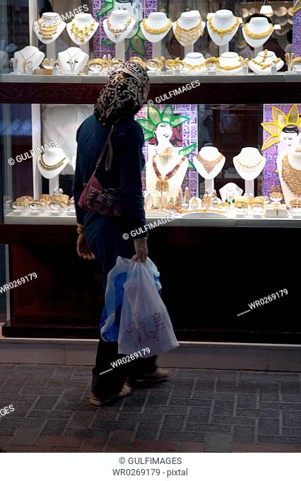 Arab Lady looking at the jewelry glass display