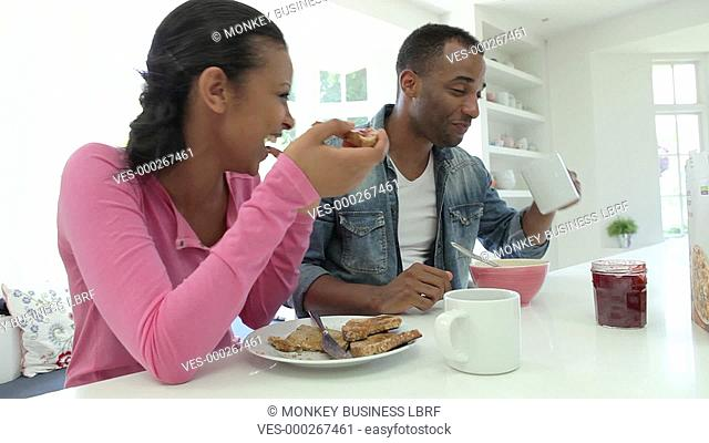 Couple enjoying breakfast in kitchen together.Shot on Canon 5d Mk2 with a frame rate of 25fps