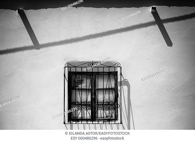 Window with a grate Andalusian house  El Pozo de Los Frailes  Parque Natural del Cabo de Gata, Almería, Andalusia, Spain  Black and white  Lights and shadows