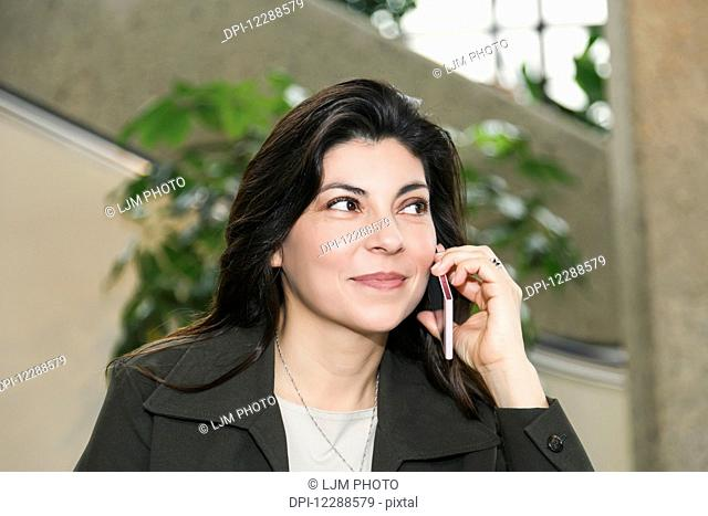 Mature business woman talking on her cell phone while taking a break in the atrium of an office building; Edmonton, Alberta, Canada