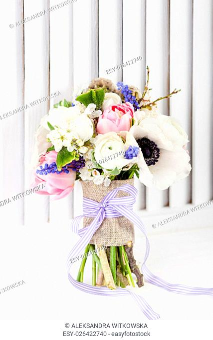 Bouquet from pink tulips, violet grape hyacinths, white anemones, violet veronica and white buttercup with violet ribbon on white wooden