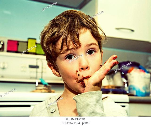 A young boy licking fingers after making fudge; Langley, British Columbia, Canada