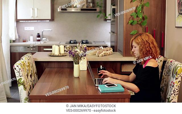 Young woman using laptop and smartphone at home office