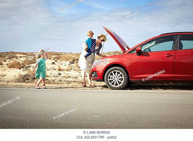 Mother examining broken down car