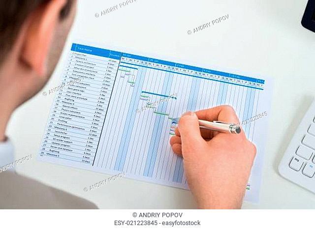 Close-up Of Businessman With Gantt Diagram At Desk
