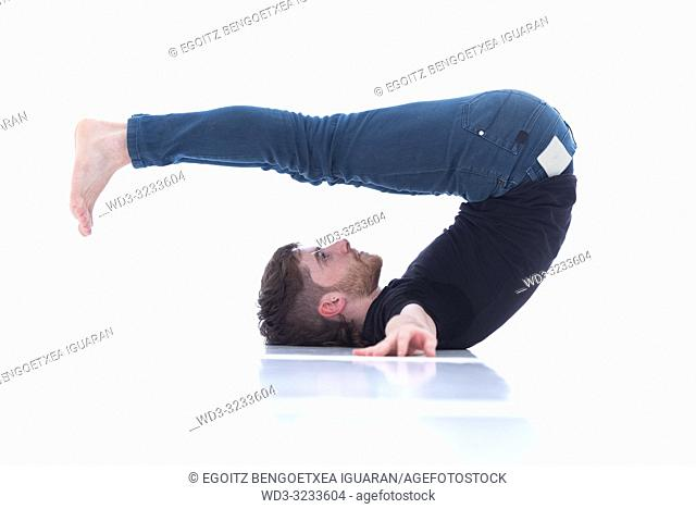 Casual dressed young adult man stretching on white background