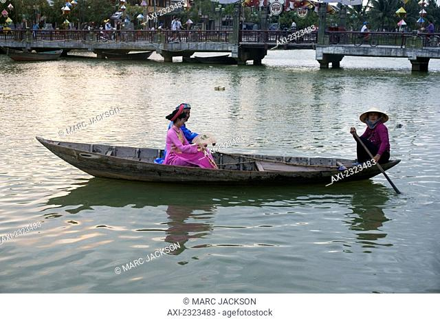 Vietnam, Vietnamese couple in traditional dress in boat; Hoi An
