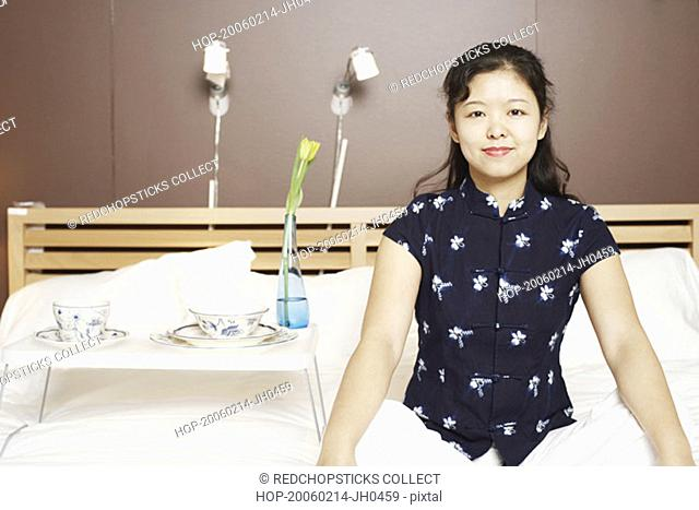 Portrait of a young woman sitting cross-legged on the bed smiling